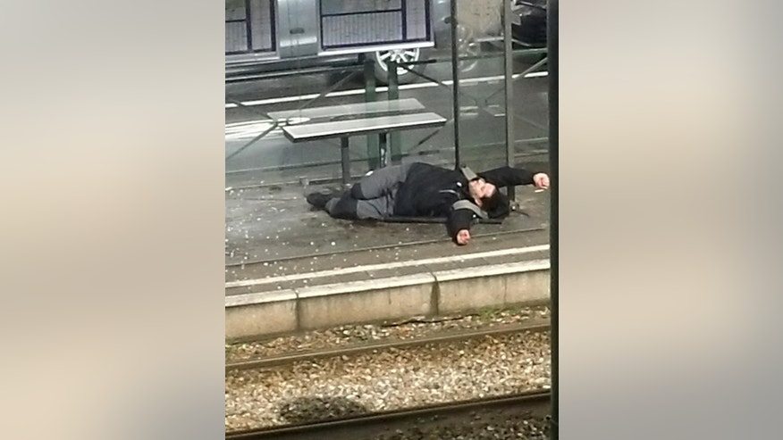 An injured man lays on the floor at a tram stop in Brussels, Belgium, Friday March 25, 2016. Police again raided a number of Brussels neighbourhoods on Friday in an operation a local official said was linked to both the airport and metro bombings and to the arrest in the Paris suburbs of a man who may have been plotting a new attack in France. (S. Kuplan via AP)