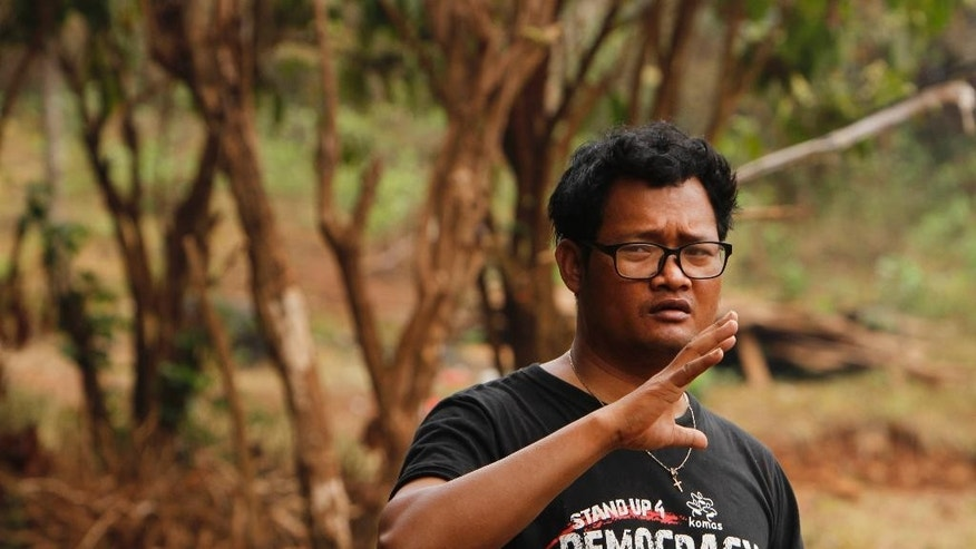In this Feb. 26, 2015, photo, Neth Prak, 34, an informal representative for the indigenous Bunong community in Bousra commune, speaks in his home village in eastern Cambodia's Mondulkiri province. About 800 Bunong families were displaced from their ancestral land to make way for government-granted rubber plantations meant to bring wealth to the poor area. But the long-term land leases have cut them off from a vital source of food, income and self-identity, bringing mostly hardship and loss. (AP Photo/Heng Sinith)