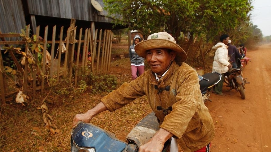 In this Feb. 26, 2015, photo, a member of the Bunong tribe walks his motorbike in Bousra, in Mondulkiri province, in eastern Cambodia. Despite promised development as part of rubber plantations in the area, many roads in the area are still dirt, sometimes impassable in rainy season. (AP Photo/Heng Sinith)