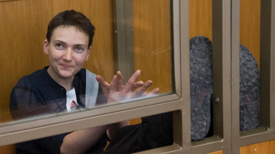 Ukrainian pilot Nadezhda Savchenko applauds and smiles in a glass cage inside court, in the town of Donetsk, Rostov-on-Don region, Russia, Tuesday, March 22, 2016. The Ukrainian pilot who is charged with complicity to murder in the deaths of two Russian journalists in war-torn eastern Ukraine has arrived to court in southwestern Russia where the verdict in her trial is due to continue. Nadezhda Savchenko served in a volunteer battalion against Russia-backed rebels and was captured by separatist rebels in July 2014 before she surfaced in Russia.  (AP Photo/Ivan Sekretarev)