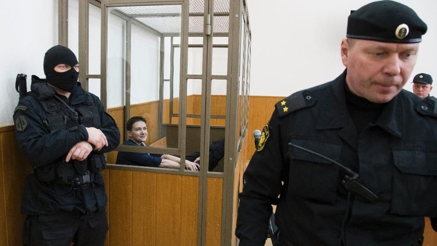 Ukrainian pilot Nadezhda Savchenko sits in a glass cage inside court, in the town of Donetsk, Rostov-on-Don region, Russia, Tuesday, March 22, 2016. The Ukrainian pilot who is charged with complicity to murder in the deaths of two Russian journalists in war-torn eastern Ukraine has arrived to court in southwestern Russia where the verdict in her trial is due to continue. Nadezhda Savchenko served in a volunteer battalion against Russia-backed rebels and was captured by separatist rebels in July 2014 before she surfaced in Russia.  (AP Photo/Ivan Sekretarev)