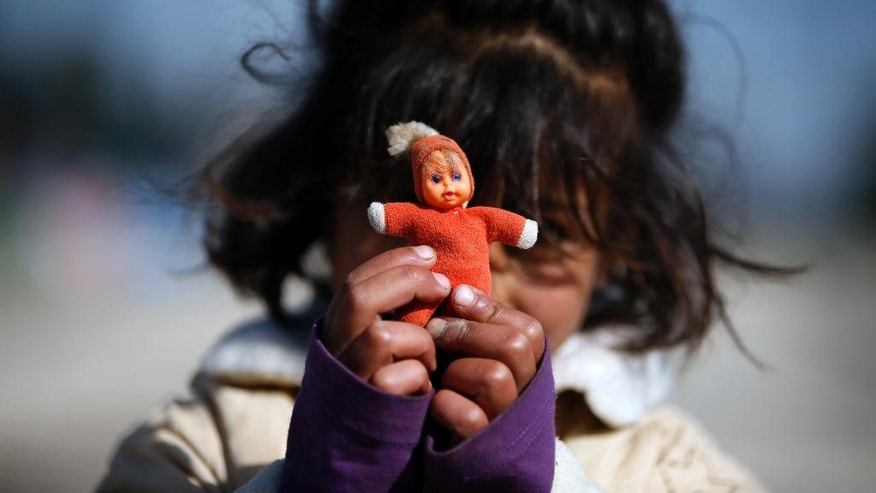 A migrant girl shows her doll in the makeshift refugee camp at the northern Greek border point of Idomeni, Greece, Saturday, March 26, 2016. Greece's border with Macedonia has been shut to refugees since earlier this month after a string of countries shut down the route which migrants used to go from Greece to central and northern Europe. Those stranded in the camp and surrounding fields have been living in dire conditions in small tents pitched in muddy fields. (AP Photo/Darko Vojinovic)
