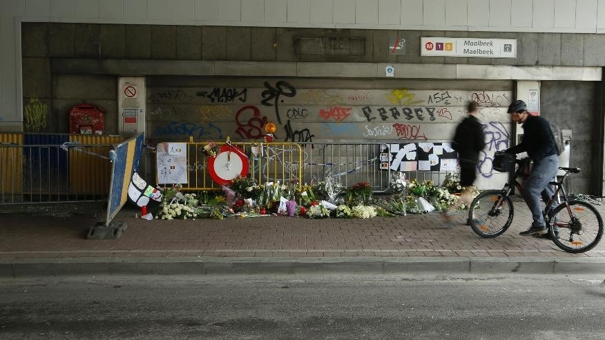 Joggers and a cyclist pass floral tributes placed outside the Maelbeek metro station, the scene of one of the bomb attacks on the Belgian capital, in Brussels, Saturday, March 26, 2016. Brussels airport officials say flights won't resume before Tuesday as they assess the damage caused by twin explosions in the terminal earlier this week. (AP Photo/Alastair Grant)