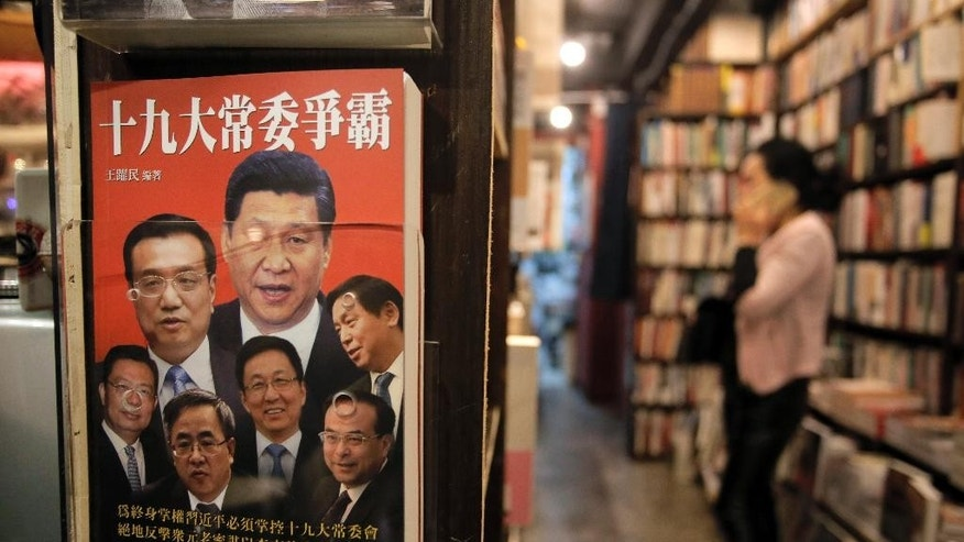 In this Jan. 7, 2016 photo, a book featuring a photo of Chinese President Xi Jinping, center top, and other senior Chinese officials on the cover is displayed at a book shop in Hong Kong. For decades, Hong Kong thrived as an Asian business hub thanks to its killer combination of Western freedoms, independent courts and closeness to mainland China's booming market. Now political and economic ills from the mainland are eroding that edge. (AP Photo/Vincent Yu)