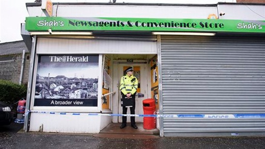 A police officer stands outside the shop where Asad Shah worked in Glasgow, Saturday March 26, 2016. (John Linton/PA via AP)