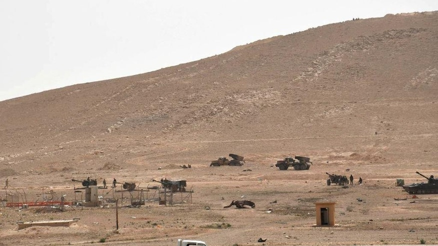 In this photo released on Thursday,  March 24, 2016, by the Syrian official news agency SANA, Syrian government forces deploy at the entrance of Palmyra, central Syria. Syrian government forces recaptured a Mamluk-era citadel in Palmyra from the extremist Islamic State group on Friday, Syrian state media and monitoring groups said, as the fierce battle for control of the historic town entered its third day. (SANA via AP)