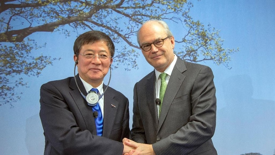 FILE - In this Feb. 3, 2016, file photo, Ren Jianxin, left, chairman of ChemChina (China National Chemical Corporation), and Michel Demare, chairman of the Board of Directors of Syngenta, pose for a photo after an annual press conference of agrochemical company Syngenta in Basel, Switzerland. The tycoon who is offering $43 billion for Swiss agrochemicals giant Syngenta keeps a low profile but is China's most aggressive dealmaker. (Georgios Kefalas/Keystone via AP, File)