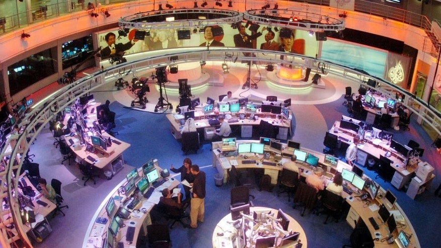 FILE- In This Tuesday, Nov. 14, 2006 file photo, Al Jazeera English Channel staff prepare for the broadcast inside the news room in Doha, Qatar. Al-Jazeera, the Qatar-based broadcaster, said Sunday, March 27, 2016 it is slashing about 500 jobs worldwide little more than two months after shutting its U.S. offshoot. (AP Photo/ Hamid Jalaudin, File)