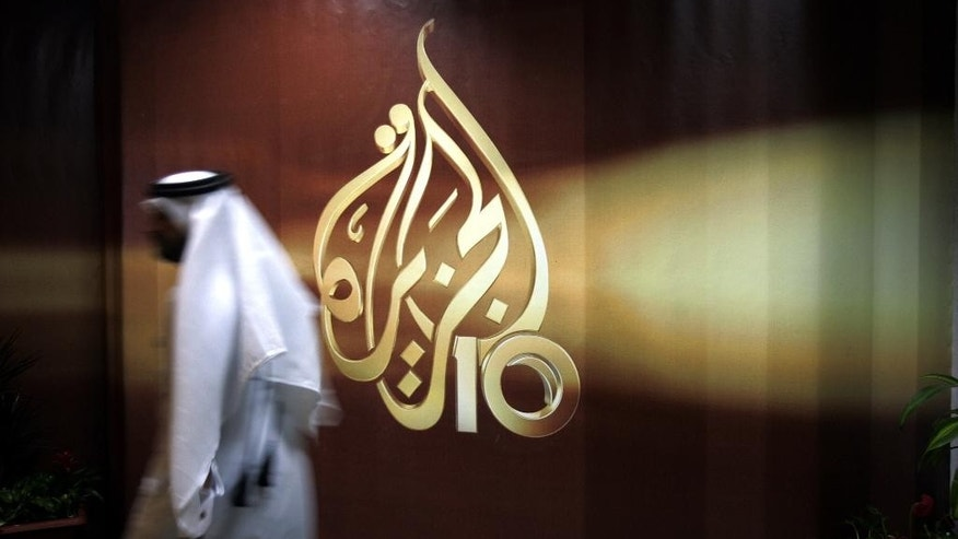 FILE- In this Wednesday Nov. 1, 2006 file photo, a Qatari employee of Al Jazeera Arabic language TV news channel walks past the logo of Al Jazeera in Doha. Al-Jazeera, the Qatar-based broadcaster, said Sunday, March 27, 2016 it is slashing about 500 jobs worldwide little more than two months after shutting its U.S. offshoot. (AP Photo/Kamran Jebreili, File)
