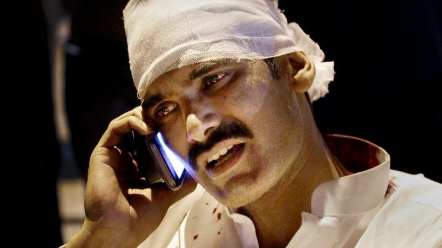A Pakistani injured man from a bomb blast talks on his cell phone at a local hospital in Lahore, Pakistan, Sunday, March, 27, 2016. A bomb blast in a park in the eastern Pakistani city of Lahore has killed tens of people and wounded scores, a health official said. (AP Photo/K.M. Chuadary)