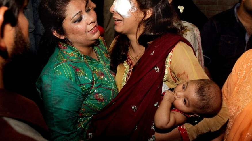 A woman injured in the bomb blast is comforted by a family member at a local hospital in Lahore, Pakistan, Sunday, March, 27, 2016. A bomb blast in a park in the eastern Pakistani city of Lahore has killed tens of people and wounded scores, a health official said. (AP Photo/K.M. Chuadary)