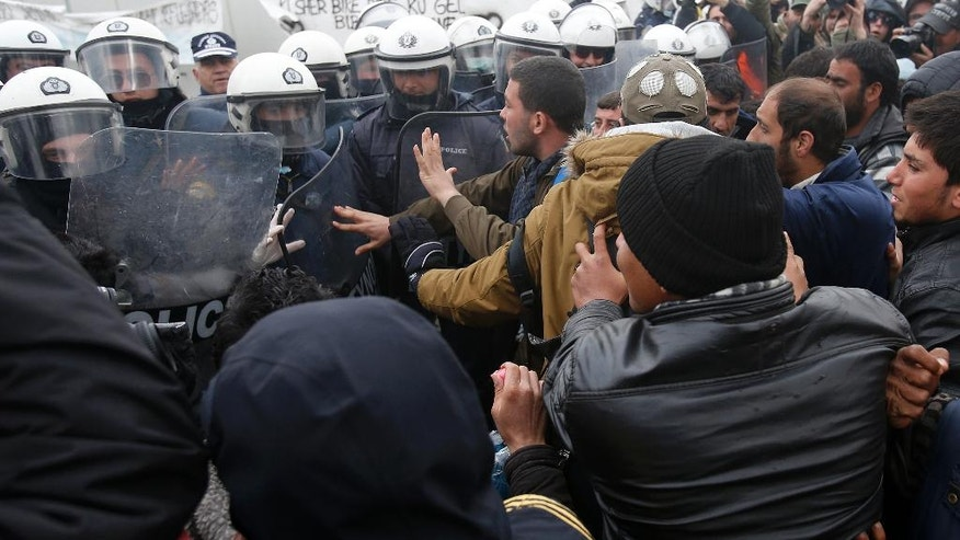 Migrants scuffle with police during a protest demanding the opening of the border between Greece and Macedonia in the northern Greek border station of Idomeni, Greece, Sunday, March 27, 2016. A split appears to have developed among the groups of migrants at the Idomeni border encampment, with Greek riot police who, so far, have used only their shields to protect the border. (AP Photo/Darko Vojinovic)