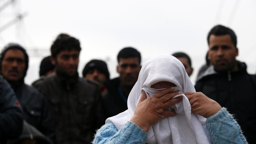 A migrant woman reacts during a protest demanding the opening of the border between Greece and Macedonia in the northern Greek border station of Idomeni, Greece, Sunday, March 27, 2016.  A split appears to have developed among the groups of migrants at the Idomeni border encampment, with Greek riot police who, so far, have used only their shields to protect the border. (AP Photo/Darko Vojinovic)