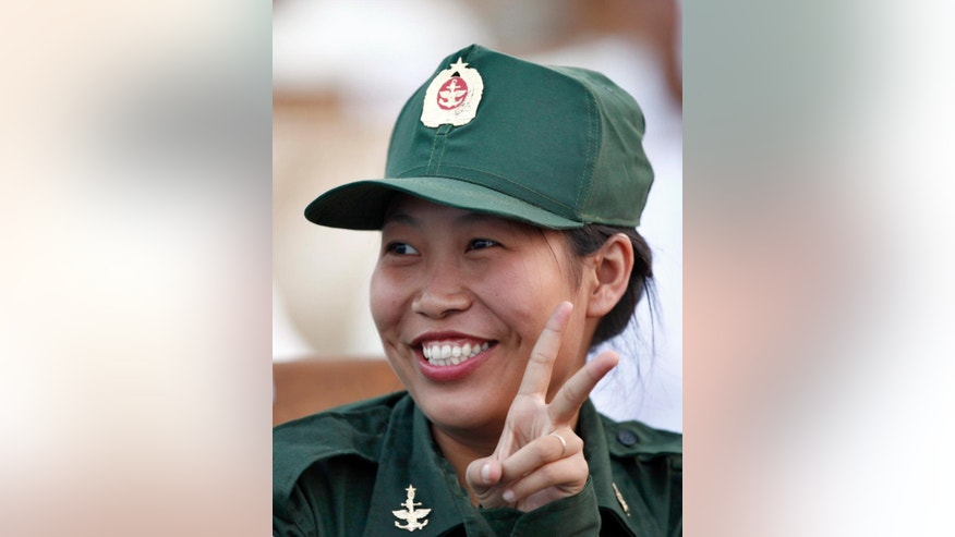 A female military officer gestures during a parade to commemorate 71st Armed Forces Day in Naypyitaw, Myanmar, Sunday, March 27, 2016. General Min Aung Hlaing, addressed the parade saying that principles of democracy mean holding elections that some parties win and others lose. It is the first time the event has been held since Aung San Suu Kyi's National League for Democracy (NLD) party became the ruling party winning November 2015 elections.(AP Photo/Aung Shine Oo)