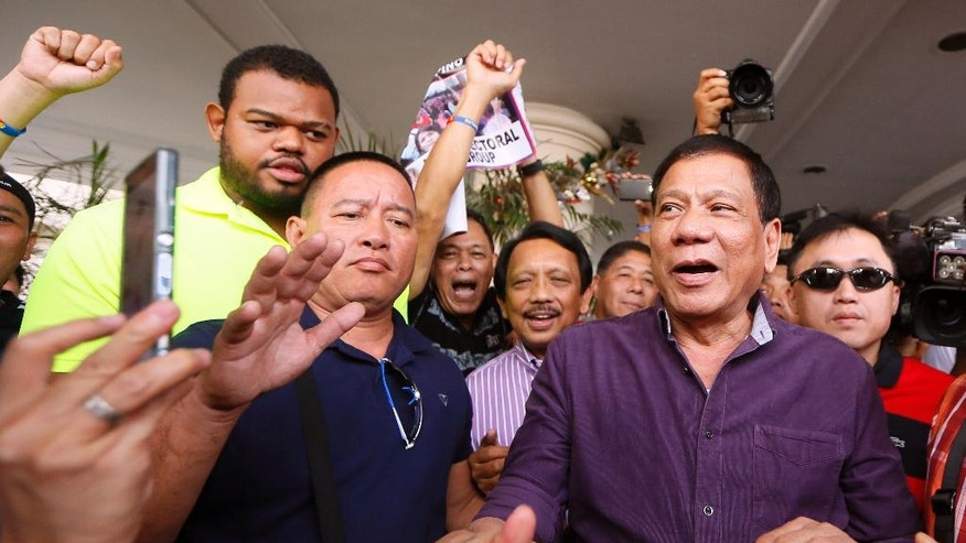 "In this Nov.30, 2015 photo, Davao City Mayor Rodrigo Duterte, right, greets supporters during his proclamation as the PDP-Laban Party's standard-bearer for the May 9, 2016 presidential elections in Manila, Philippines.  Nicknamed ""Duterte Harry,"" after a Clint Eastwood character with little regard for rules, the Philippine city mayor casually threatens to shoot criminals, hang them like dirty laundry or drown them in Manila Bay. His expletives have sideswiped even the deeply revered pope. Despite such brazen talk, Rodrigo Duterte has emerged as a top contender in Philippine presidential elections on May 9 in an impressive political rise that has been likened to Donald Trump's. The tough-talking mayor finds the comparison offensive and draws the line. (AP Photo/Bullit Marquez)"