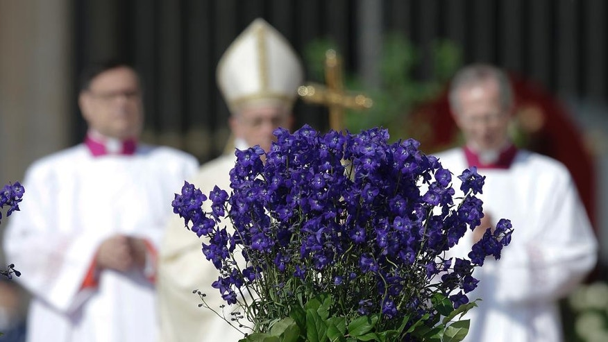Pope Francis, center, framed by flowers, walks with his pastoral staff as he arrives to celebrate the Easter mass in St. Peter's Square, at the Vatican, Sunday, March 27, 2016. (AP Photo/Gregorio Borgia)