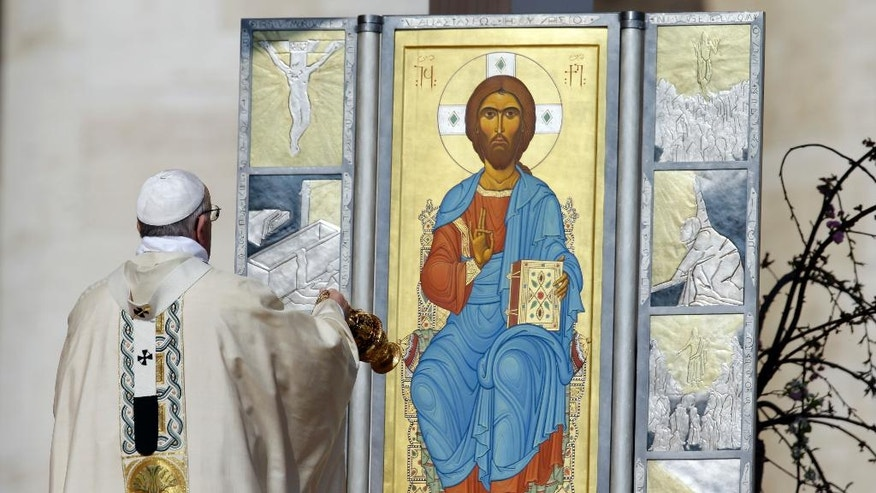 Pope Francis asperges incense in front of an icon of Jesus as he celebrates the Easter mass in St. Peter's Square, at the Vatican, Sunday, March 27, 2016. (AP Photo/Gregorio Borgia)