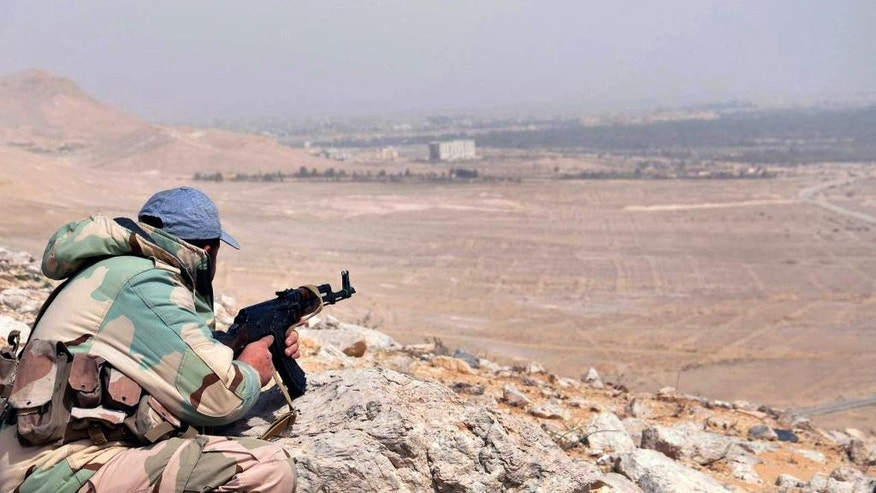 In this photo released on Thursday, March 24, 2016, by the Syrian official news agency SANA, a Syrian government soldier takes his position on hill at the entrance of Palmyra, central Syria. Syrian government forces recaptured a Mamluk-era citadel in Palmyra from the extremist Islamic State group on Friday, Syrian state media and monitoring groups said, as the fierce battle for control of the historic town entered its third day. (SANA via AP)
