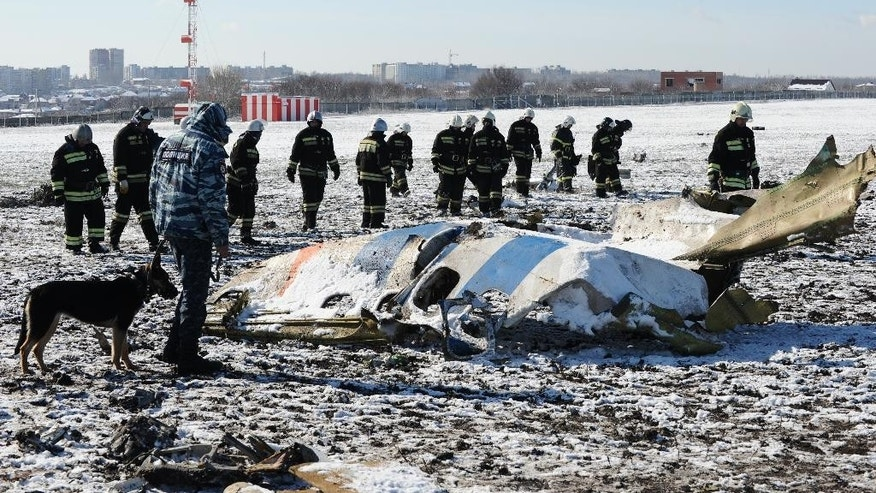 "FILE - In this Sunday, March 20, 2016 file photo, Russian Emergency Ministry employees investigate the wreckage of a crashed plane at the Rostov-on-Don airport, south of Moscow, Russia. Investigators have successfully downloaded all the information from the flight recorders on the FlyDubai plane that crashed in southern Russia and determined it is in a ""satisfactory"" state, the United Arab Emirates' aviation regulator said Sunday, March 27, 2016. (AP Photo, File)"