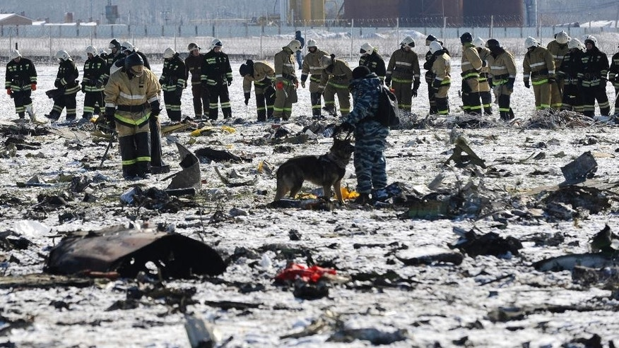 "FILE - In this Sunday, March 20, 2016 file photo, Russian Police and Emergency Ministry employees investigate the wreckage of a crashed plane at the Rostov-on-Don airport, about 950 kilometers (600 miles) south of Moscow, Russia, Sunday, March 20, 2016. Investigators have successfully downloaded all the information from the flight recorders on the FlyDubai plane that crashed in southern Russia and determined it is in a ""satisfactory"" state, the United Arab Emirates' aviation regulator said Sunday, March 27, 2016.  (AP Photo, File)"
