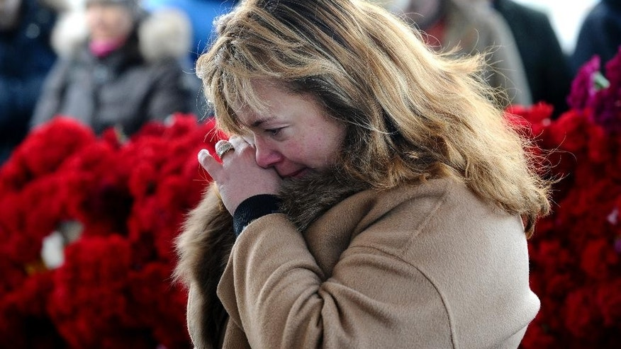 "FILE - In this Sunday, March 20, 2016 file photo, A woman mourns after putting flowers in memory for the victims of the crashed FlyDubai plane at the Rostov-on-Don airport, about 950 kilometers (600 miles) south of Moscow, Russia. Investigators have successfully downloaded all the information from the flight recorders on the FlyDubai plane that crashed in southern Russia and determined it is in a ""satisfactory"" state, the United Arab Emirates' aviation regulator said Sunday, March 27, 2016. (AP Photo, File)"