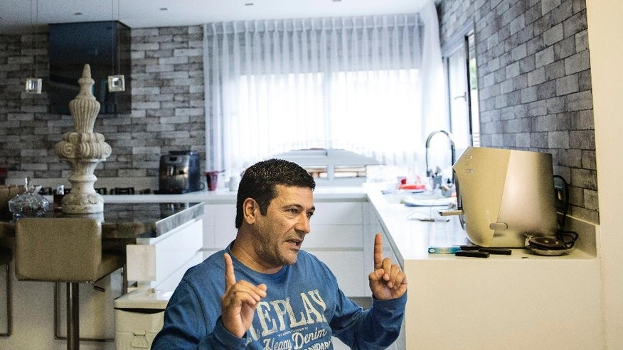In this Tuesday, Nov. 10, 2015, photo, convicted con man Gilbert Chikli gestures during an interview with the Associated Press at his house in the port city of Ashdod, Israel. Chikli is widely credited with inventing a con that has inspired a generation of copycats. Chikli's scam, called the fake president, fake CEO or business email compromise scam, has cost companies around the world $1.8 billion in just over two years, according to the FBI. (AP Photo/Tsafrir Abayov)