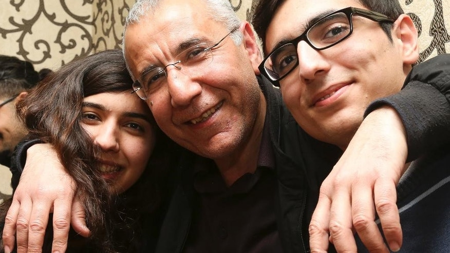 Human rights activist Intigam Aliyev, center, poses for a photo with his son and daughter upon his release at home in Baku, Azerbaijan, Monday, March 28, 2016. A court in Azerbaijan has ordered the release of a human rights activist who spent the last two years in jail. Aliyev was convicted last year of economic crimes that critics have dismissed as retaliation for his work. (AP Photo/Aziz Karimov)