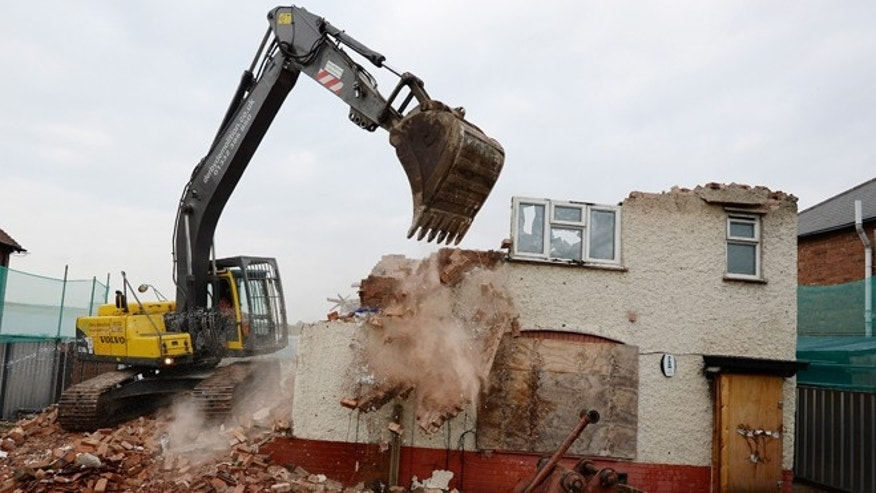 DERBY, UNITED KINGDOM - SEPTEMBER 30:  Builders begin to demolish the semi-detached house at 18 Victory Road where six children died in a fire started by their parents Mick and Mairead Philpott in Allenton on September 30, 2013 in Derby, England. The Philpotts were jailed in April, along with friend Paul Mosley, after being convicted of killing the couple's six children by setting fire to the three-bedroom semi-detached house in May 2012.  (Photo by Nigel Roddis)