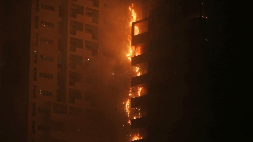 Fire and smoke billow from a high-rise building in Ajman, United Arab Emirates, early Tuesday, March 29, 2016.  Police in the United Arab Emirates city of Ajman confirmed the fire erupted at the high-rise tower, the latest in a series of skyscraper blazes in the Gulf nation, but gave no details of casualties.   (AP Photo/Kamran Jebreili)