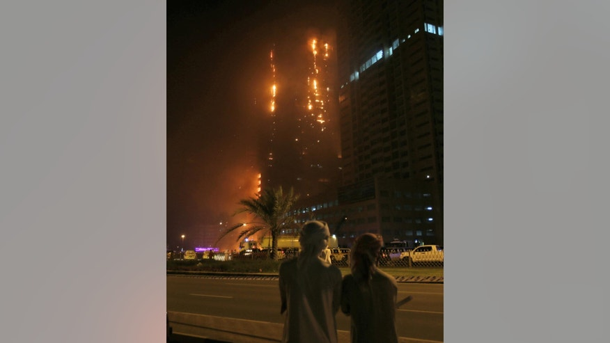 People gather to watch a high-rise building as a fire spreads up the side of the building in Ajman, United Arab Emirates, early Tuesday, March 29, 2016.  Police in the United Arab Emirates city of Ajman confirmed the fire erupted at the high-rise tower, the latest in a series of skyscraper blazes in the Gulf nation, but gave no details of casualties. (AP Photo/Kamran Jebreili)