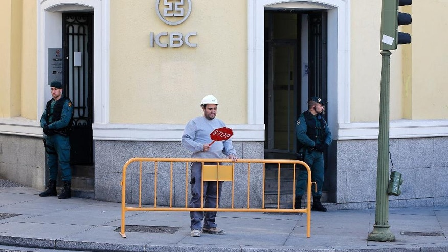 FILE - In this Wednesday, Feb. 17, 2016, file photo, Spanish Civil Guards stand outside an Industrial and Commercial Bank of China, or ICBC, branch in Madrid, Spain. In February, Spain arrested six executives from ICBC, China's largest bank for allegedly facilitating a Chinese money laundering network that sold its services to Spanish and Chinese criminal syndicates in Europe, according to Europol, which is also investigating the network's links to France, Germany and Lithuania. (AP Photo/Paul White, File)