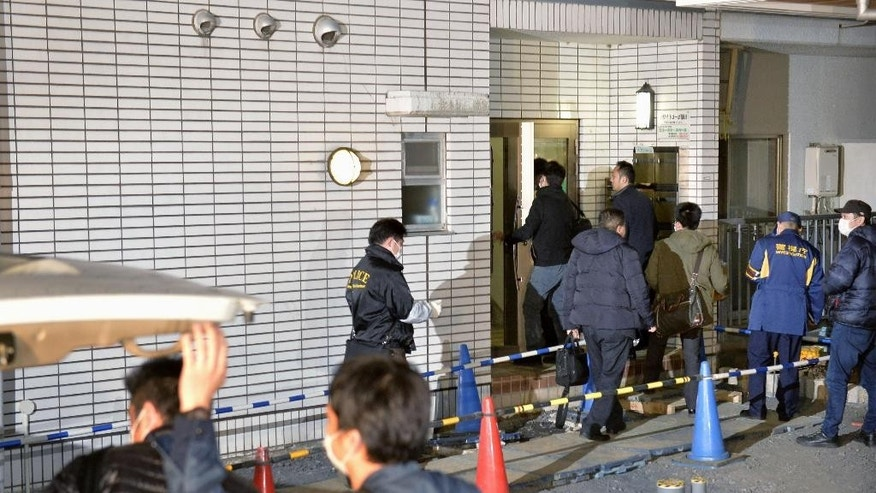 March 28, 2016: Police officers arrive for investigation of the apartment of abduction suspect Kabu Terauchi in Tokyo.