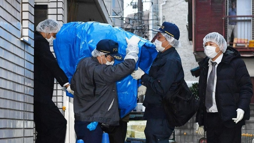 March 28, 2016: Police officers carry a sheet-covered computer from the apartment of abduction suspect Kabu Terauchi in Tokyo.