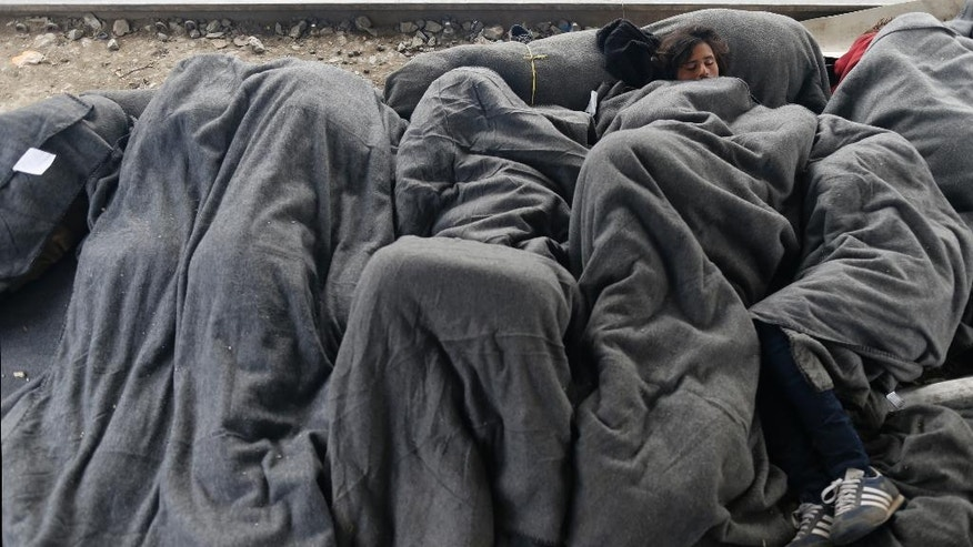 Migrants sleep on train tracks near the makeshift refugee camp at the northern Greek border point of Idomeni, Greece, Monday, March 28, 2016. Over 11,000 refugees and migrants stranded at this makeshift encampment, some for weeks, after Balkan countries on what used to be the busiest migrant route to central and northern Europe shut down their borders. (AP Photo/Darko Vojinovic)
