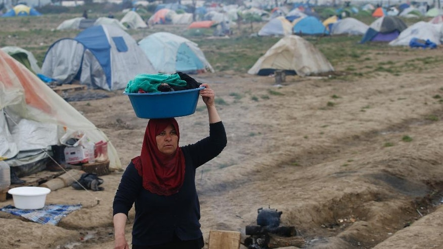 A woman walks through the makeshift refugee camp at the northern Greek border point of Idomeni, Greece, Monday, March 28, 2016. Over 11,000 refugees and migrants stranded at this makeshift encampment, some for weeks, after Balkan countries on what used to be the busiest migrant route to central and northern Europe shut down their borders. (AP Photo/Darko Vojinovic)