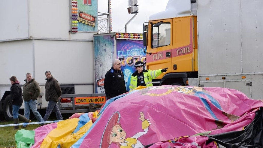 Police and forensic officers attend the scene Sunday, March 27, 2016, where a seven-year old girl died after she was blown by the wind about 150 metres on a bouncy castle on Saturday. The children's bouncy castle is thought to have been swept away by a gust of wind as families gathered for an Easter fair, over the long holiday weekend. (Stefan Rousseau / PA via AP) UNITED KINGDOM OUT - NO SALES - NO ARCHIVES