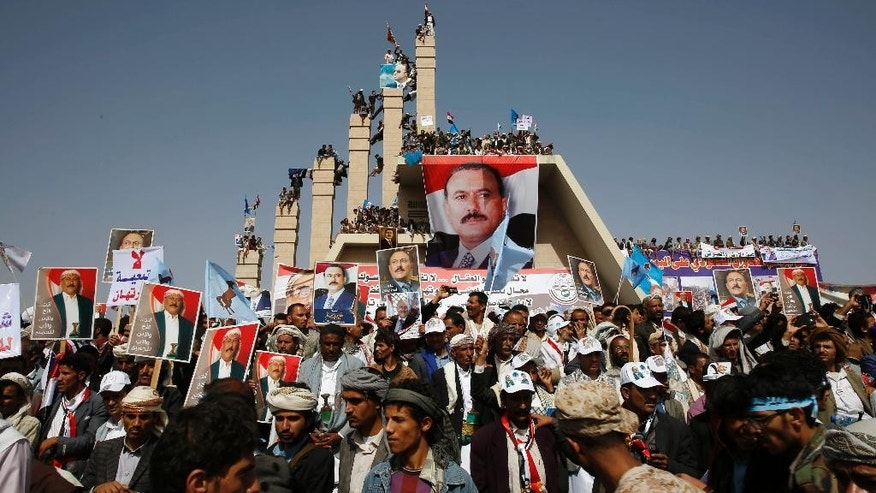 Supporters of Yemen's former President Ali Abdullah Saleh, seen in posters, who are allies of Shiite rebels known as Houthis, attend a rally to mark the first anniversary of the Saudi-led military campaign against them, in Sanaa, Yemen, Saturday, March 26, 2016. On Friday, in his first speech in months, the leader of the Houthi rebels called for street rallies to mark the occasion. Yet his tone was comparatively subdued, suggesting that the Houthis are under pressure following yearlong airstrikes and a ground operation that have killed thousands of civilians. (AP Photo/Hani Mohammed)