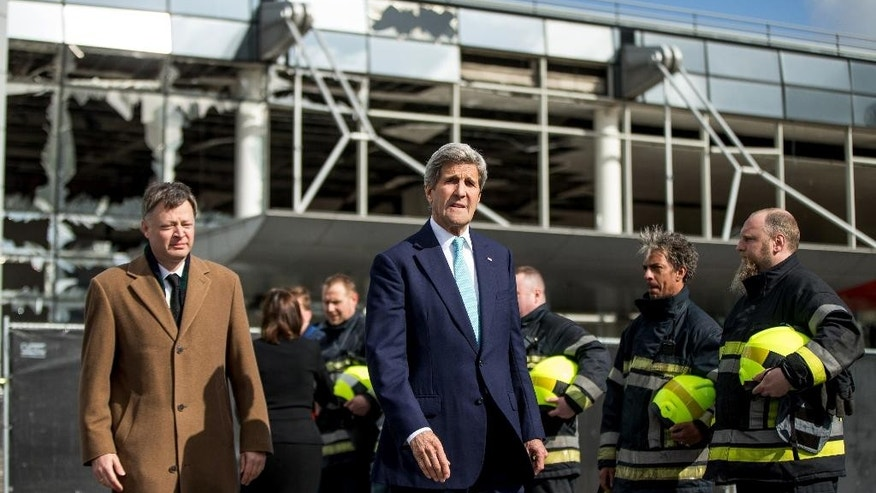 Blown out windows are seen behind as Secretary of State John Kerry arrives to participates in wreath-laying at Brussels Airport in Brussels, Belgium, Friday, March 25, 2016, paying his respect to victims of terrorist attacks that left more than 30 dead at Brussels Airport. Also pictured is Brussels Airport CEO Feist Arnaud, left. (AP Photo/Andrew Harnik, Pool)