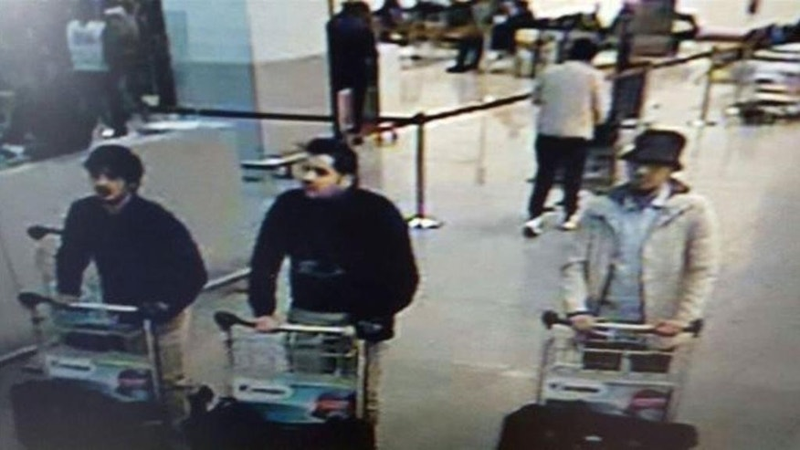 "In this image provided by the Belgian Federal Police in Brussels on Tuesday, March 22, 2016 of three men who are suspected of taking part in the attacks at Belgium's Zaventem Airport. The website of Belgium's Federal Police on Monday, March 28 began carrying a 32-second video of a mysterious man in a hat suspected of having taking part in the March 22 bombing of Brussels Airport. ""The police are seeking to identify this man,"" the site says. The implication is that the suspected accomplice of the two airport suicide bombers could still be at large. (Belgian Federal Police via AP)"