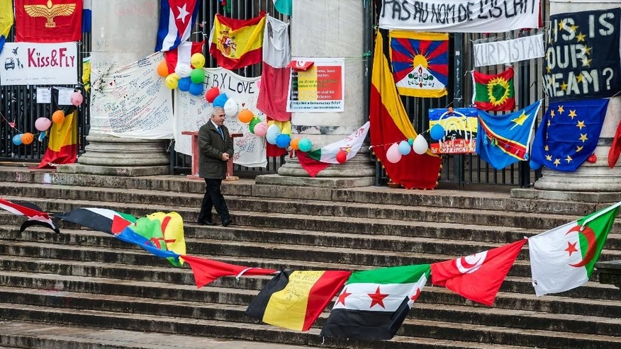 A man walks at a memorial site at the Place de la Bourse in Brussels, Sunday, March 27, 2016. In a sign of the tensions in the Belgian capital and the way security services are stretched across the country, Belgium's interior minister appealed to residents not to march Sunday in Brussels in solidarity with the victims. (AP Photo/Geert Vanden Wijngaert)