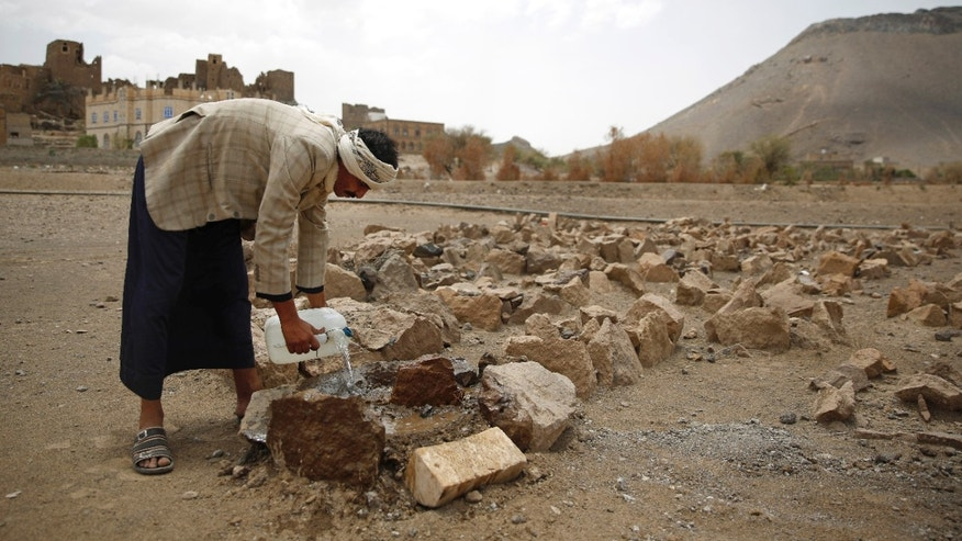Faisal Ahmed, whose son, Udai Faisal, died of severe acute malnutrition, pours water on his grave in Hazyaz village on the southern outskirts of Sanaa, Yemen.