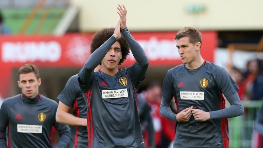 Belgium's Axel Witsel, center, and his teammates enter the pitch wearing shirts with a message remembering the victims of the recent attacks in Brussels  before a friendly soccer match between Portugal and Belgium in Leiria, Portugal, Tuesday, March 29 2016. (AP Photo/Steven Governo)
