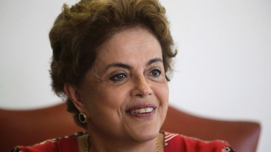 Brazil's President Dilma Rousseff smiles during a meeting with Brazilian Ambassador Roberto Azevedo, director general of the World Trade Organization, at the Planalto Presidential Palace, in Brasilia, Tuesday, March 29, 2016. Former Brazilian President Luiz Inacio Lula da Silva said Monday that he believes Rousseff, his embattled successor and protege, can survive mounting pressure in Congress for her impeachment. Rousseff recently appointed Silva as her chief of staff in a much-discussed move that still must be confirmed by Brazil's top court. (AP Photo/Eraldo Peres)