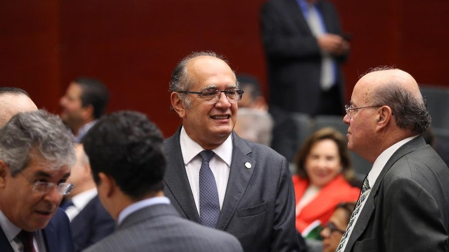Brazil'z Supreme Court Justice Gilmar Mendes smiles while waiting for the start of a legal conference in Lisbon, Tuesday, March 29, 2016. Mendes says Brazil will become harder to run if the Brazilian Democratic Movement Party confirms later Tuesday it is withdrawing its support for President Rousseff's troubled administration. (AP Photo/Armando Franca)