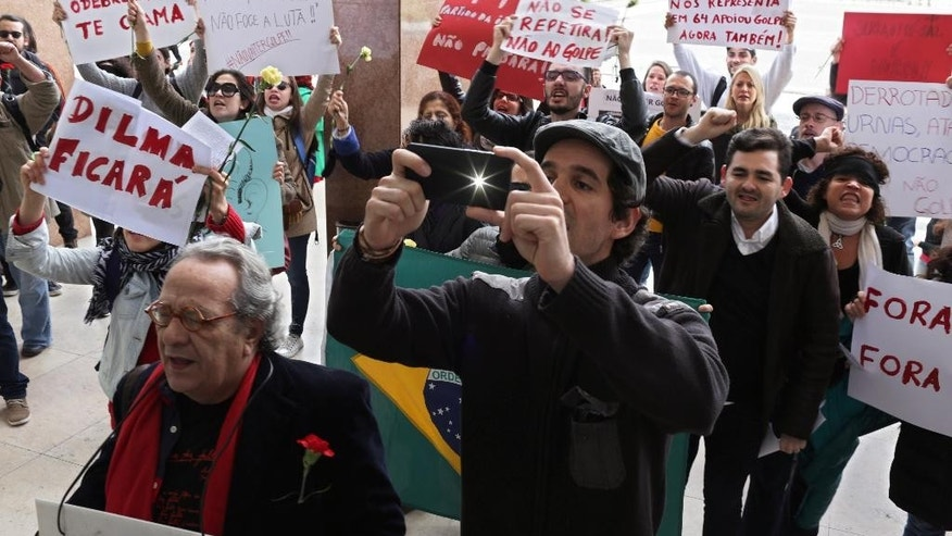 Protestors shout slogans and display posters against moves to impeach Brazilian President Dilma Roussefft outside a legal conference in Lisbon attended by top Brazilian politicians, Tuesday, March 29 2016. (AP Photo/Armando Franca)
