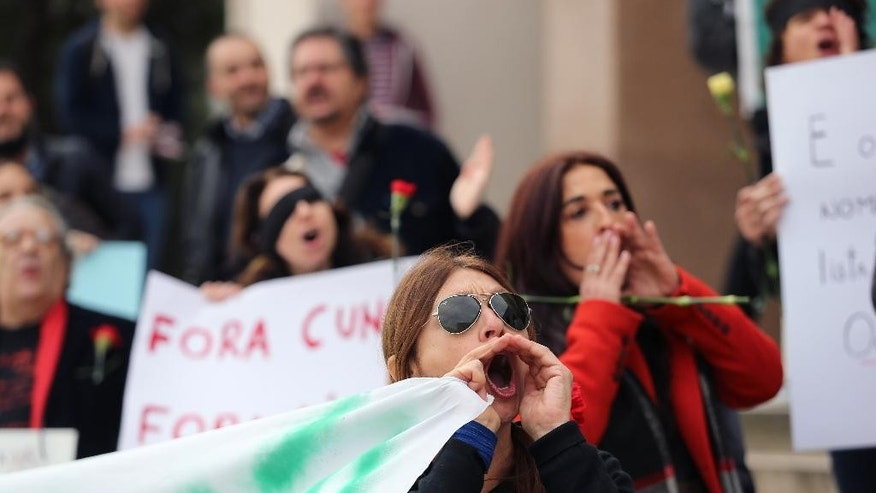 Protestors shout slogans as Brazilian Senator Jose Serra arrives for a legal conference in Lisbon, Tuesday, March 29, 2016. About 50 people, mostly Brazilians, protested outside the event, attended by top Brazilian politicians, against moves to impeach President Rousseff. (AP Photo/Armando Franca)