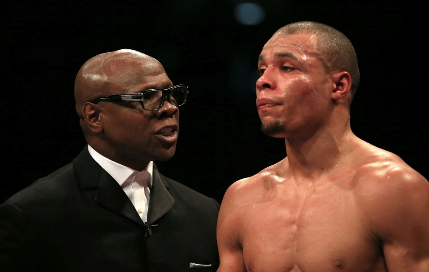 FILE - Thisis a Feb. 28, 2015 file photo of Chris Eubank Snr, left, speaks to his son Chris Eubank Jnr at the O2 Arena, London. British boxer  Nick Blackwell lies in an induced coma in a hospital in London Monday March 28, 2016  following a brutal middleweight title fight  against Chris Eubank Jnr. In 1991, Michael Watson suffered a near-fatal brain injury in an all-British world title fight against Chris Eubank Snr.  Eubank Snr.,  was in the corner of his son, Chris Eubank Jnr., who was handing Blackwell a beating in their fight for the British title at Wembley Arena.  (Nick Potts/PA via AP) UNITED KINGDOM OUT  NO SALES NO ARCHIVE