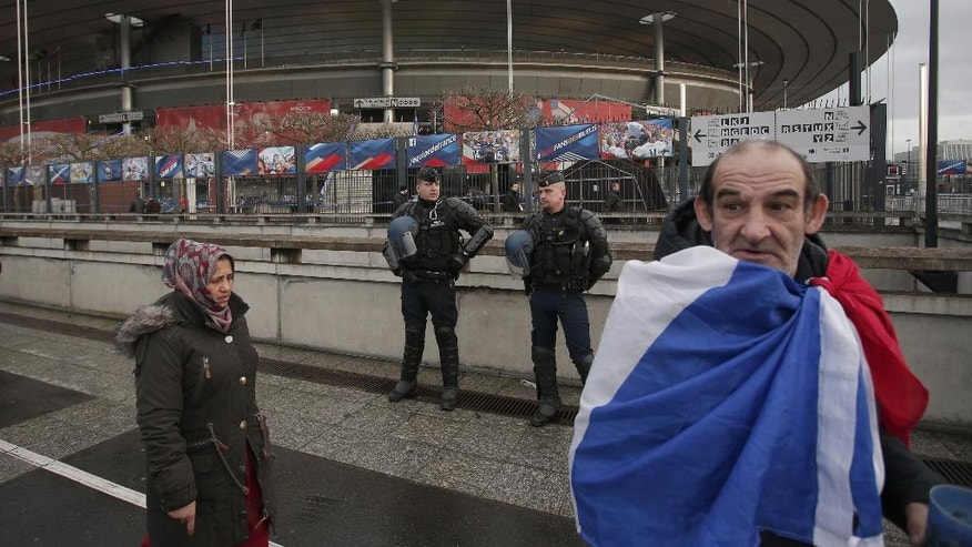 A french supporter wrapped in his national flag passes by police officers guarding the Stade de France stadium prior to the international friendly soccer match between France and Russia in Saint Denis, north of Paris, France, Tuesday, March 29, 2016. (AP Photo/Thibault Camus)