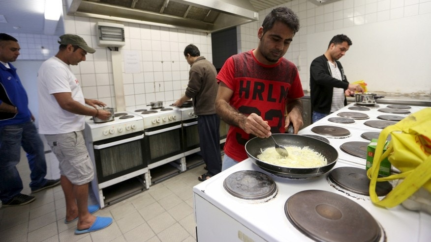 "March 24, 2016: Migrants cook in the kitchen of the accommodation for migrants ""Spree Hotel"" in Bautzen, Germany."