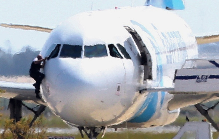 A man, leaves the hijacked aircraft of Egyptair from the pilot's window after landing at Larnaca airport Tuesday, March 29, 2016. An EgyptAir plane was hijacked  while flying from the Egyptian Mediterranean coastal city of Alexandria to the capital, Cairo, and later landed in Cyprus where some of the women and children were allowed to get off the aircraft, according to Egyptian and Cypriot officials. (AP Photo/Petros Karadjias)